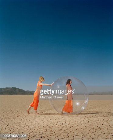 Woman in desert pushing woman in plastic bubble, side view : Stock Photo