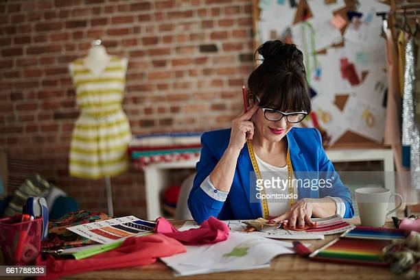 Woman in design studio sitting at desk, hand on head looking down