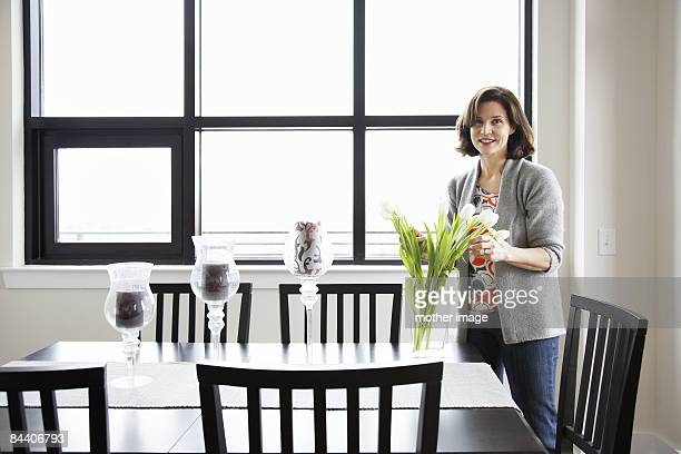 Woman in dinning room arranging flowers