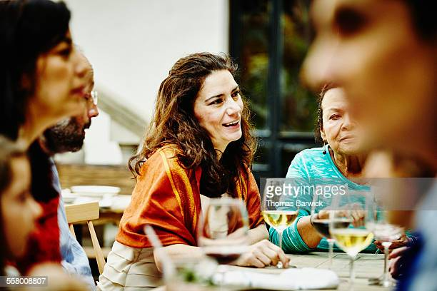 Woman in discussion with family during dinner