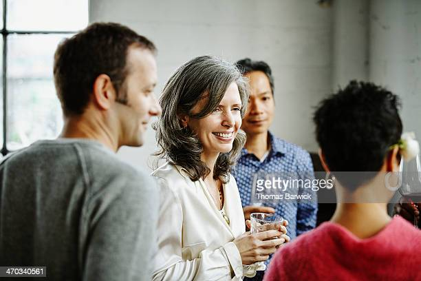 Woman in discussion with friends at dinner party