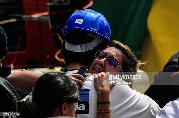 A woman in distress embraces a rescuer as she waits for news of a relative though to be buried at a flattened building in Mexico City on September 25...
