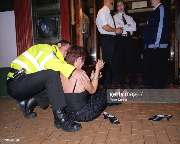 A woman in distress seated on the pavement outside a bar during a night out in Basingstoke town centre is attended to by a police officer September...