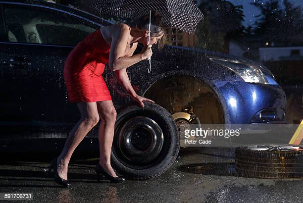 Woman in dress changing tyre in rain