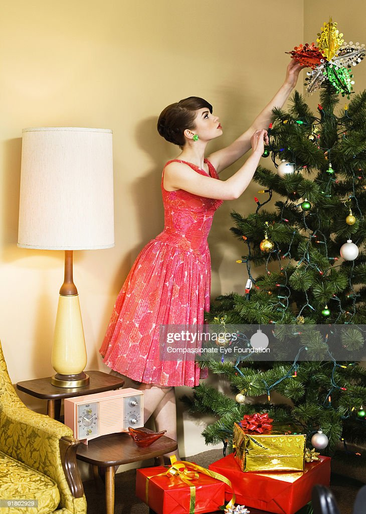 woman in dress decorating a christmas tree : Stock Photo