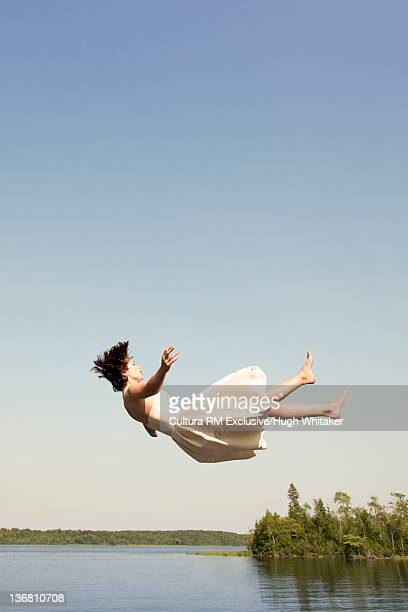 Woman in dress jumping into lake