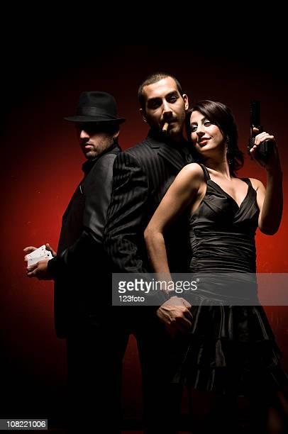 Frau im Kleid posieren mit zwei Männer mit schwarzen Anzügen