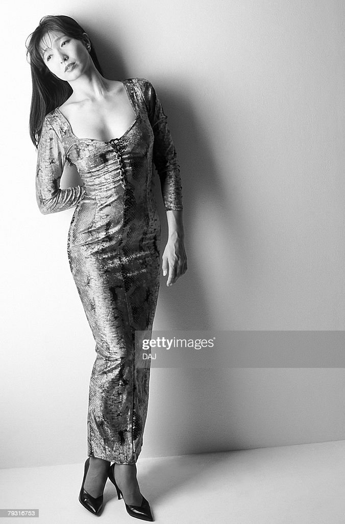Woman in dress standing and looking away, black and white, front view, white background, copy space : Stock Photo