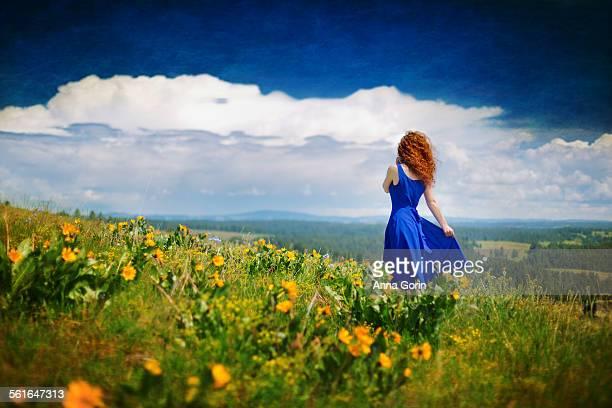 Woman in dress stands in meadow of wildflowers
