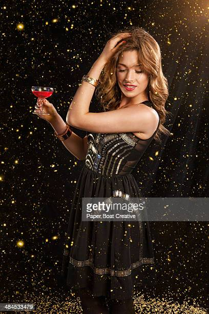 Woman in elegant black dress with gold sparkles