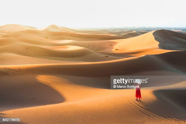 Woman in elegant dress admiring the view from a sand sune in Sahara desert, Morocco, North Africa.