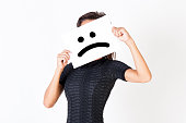 Woman in elegant dress holding dissatisfied face paper - unhappy and dissatisfied treatment concept