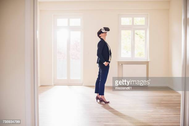 Woman in empty apartment wearing VR glasses