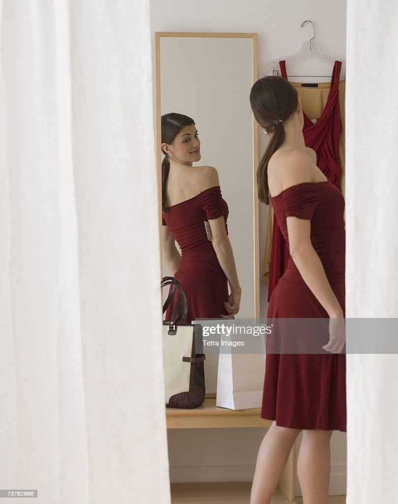 Woman in evening dress looking in mirror stock photo for Looking mirror