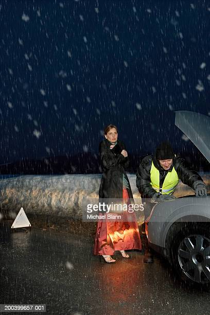 Woman in evening dress standing by mechanic working on car in snow