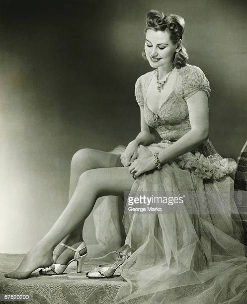 Woman in evening gown adjusting stockings, posing in studio, (B&W), portrait