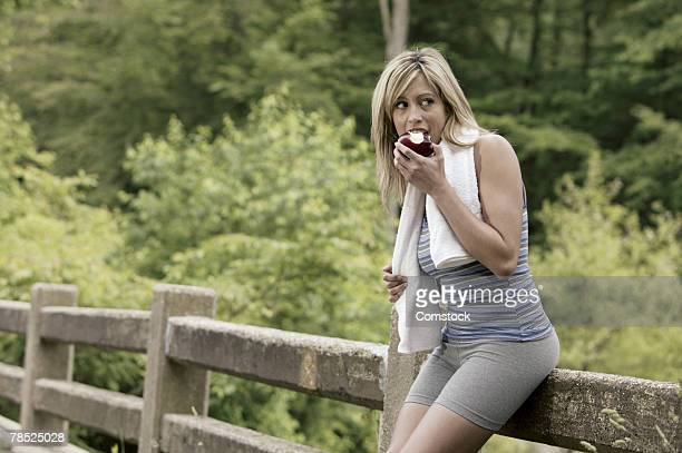 Woman in exercise gear eating apple