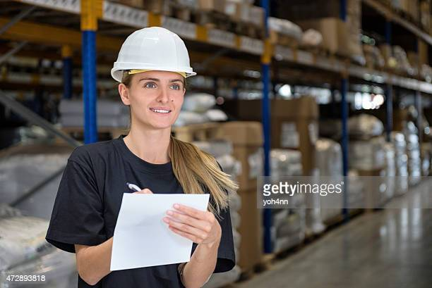 Woman in factory writes and smiles