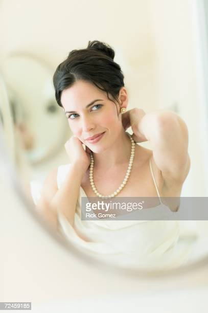 Woman in fancy clothing putting on pearl necklace
