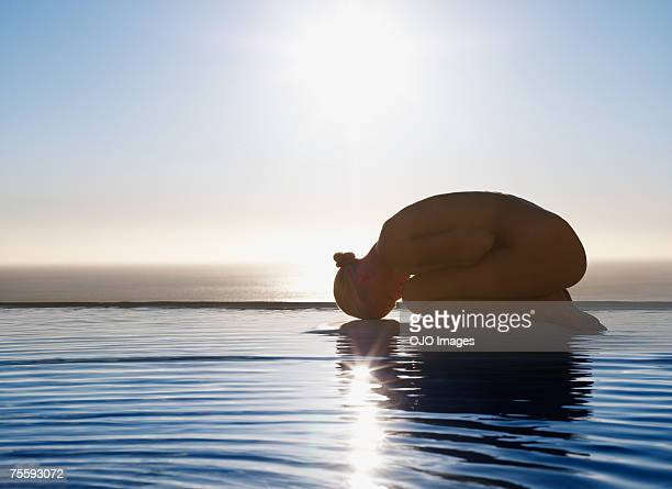 Woman in fetal position on tranquil water
