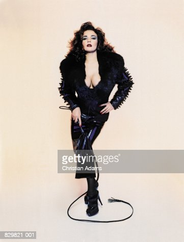 Woman in fetish wear holding whip, portrait : Stock Photo