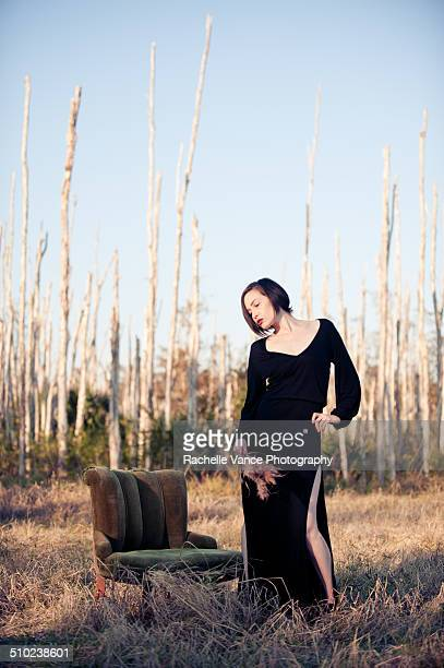 Woman in field dreaming in long black dress