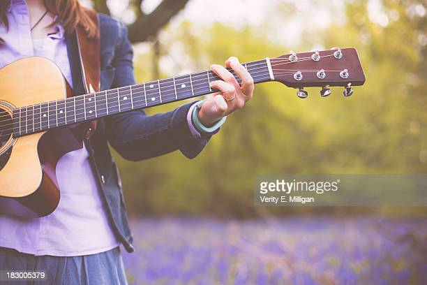 Woman in field of bluebells playing guitar