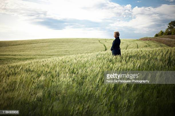 Woman in field of grain at sunset, panorama view