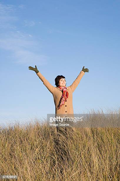 Woman in field with arms raised