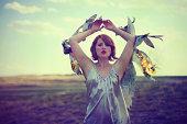 Woman in field with fiery newspaper wings