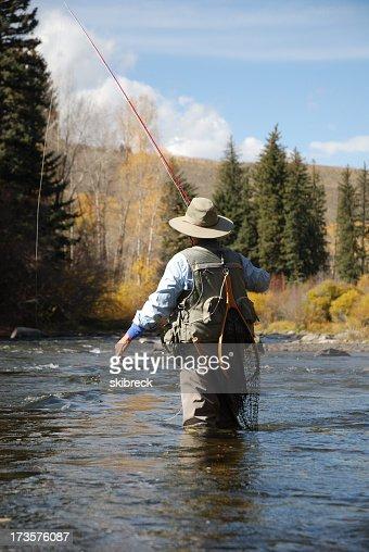 Woman in fishing gear walking in the stream