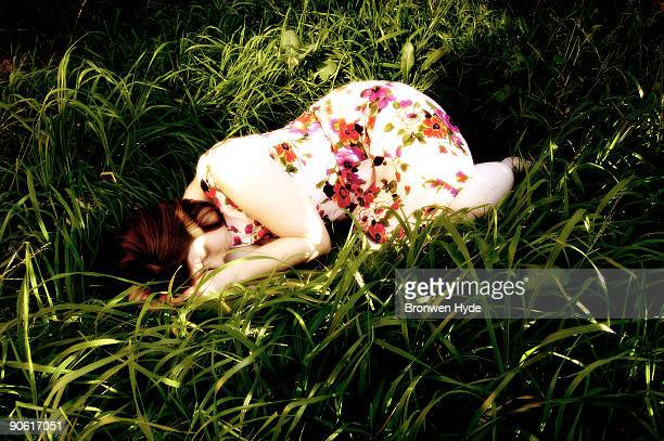 Woman in floral dress lying in the grass