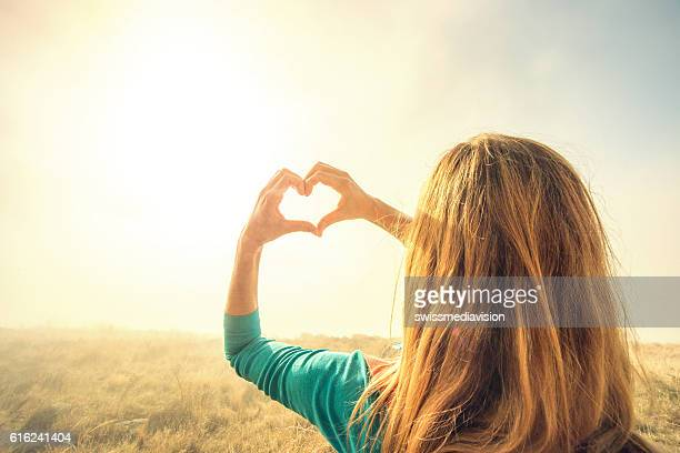 Woman in fog makes heart shape finger frame