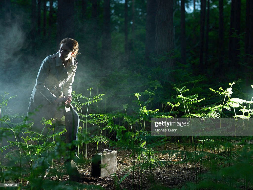 Woman in forest, digging hole near briefcase among ferns