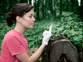Woman using white glove to check cleanliness of tree stump, green ivy in background