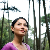 Woman in forest looking up, Cypress trees in background, close-up, portrait
