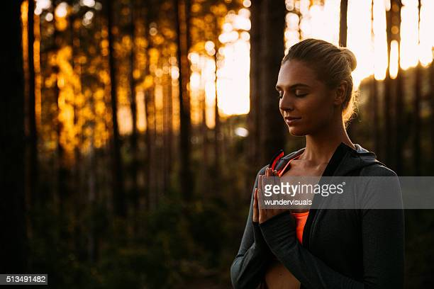 Woman in forest with her hands together doing breathing exercise