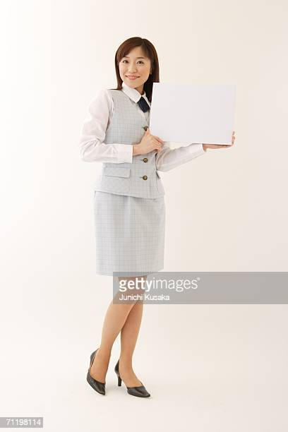 A  woman in formal attire holding a white blank message