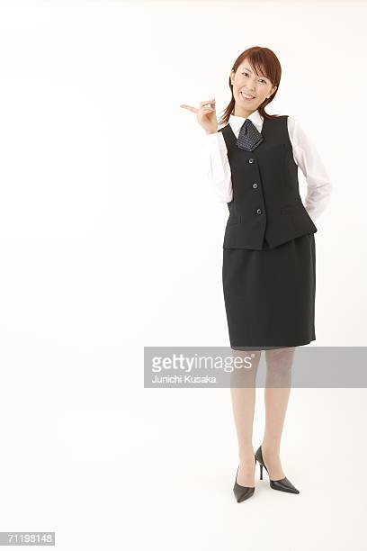 A  woman in formal attire pointing a direction