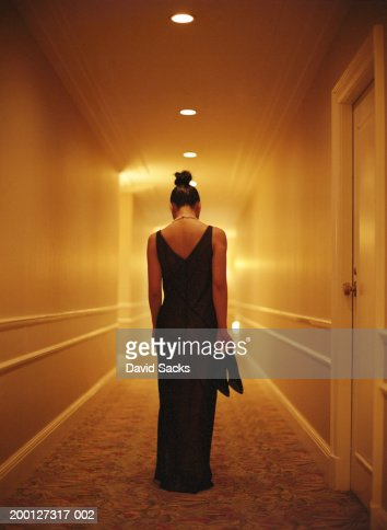 Woman in formal wear holding shoes in hallway, rear view : Stock Photo