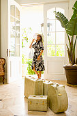 Woman in foyer with suitcases
