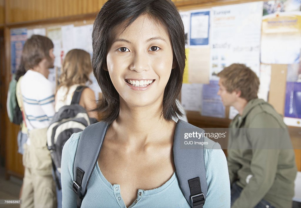 Woman in front of a bulletin board with people in the background : Stock Photo