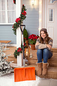 Woman resting in front of her house. Snow shovel is near. Wearing knitted sweaters, hat and boots. House, yard are decorated with festive string lights, christmas flowers. Day time, winter.