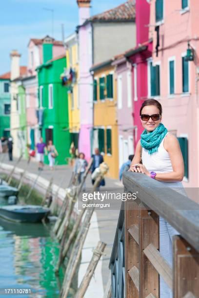 女性の前に、色彩豊かな家並み、ブラーノ、イタリア