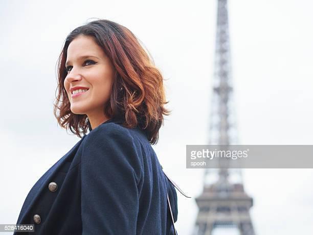 Femme en avant de la tour Eiffel à Paris
