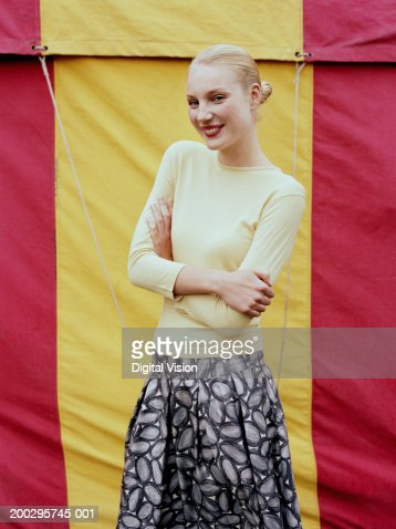 Woman in front of fairground tent, arms folded, smiling, portrait : ストックフォト