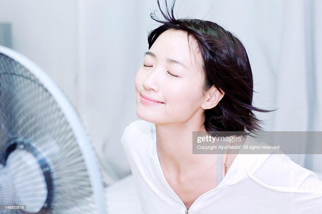Woman in front of fan : Stock Photo