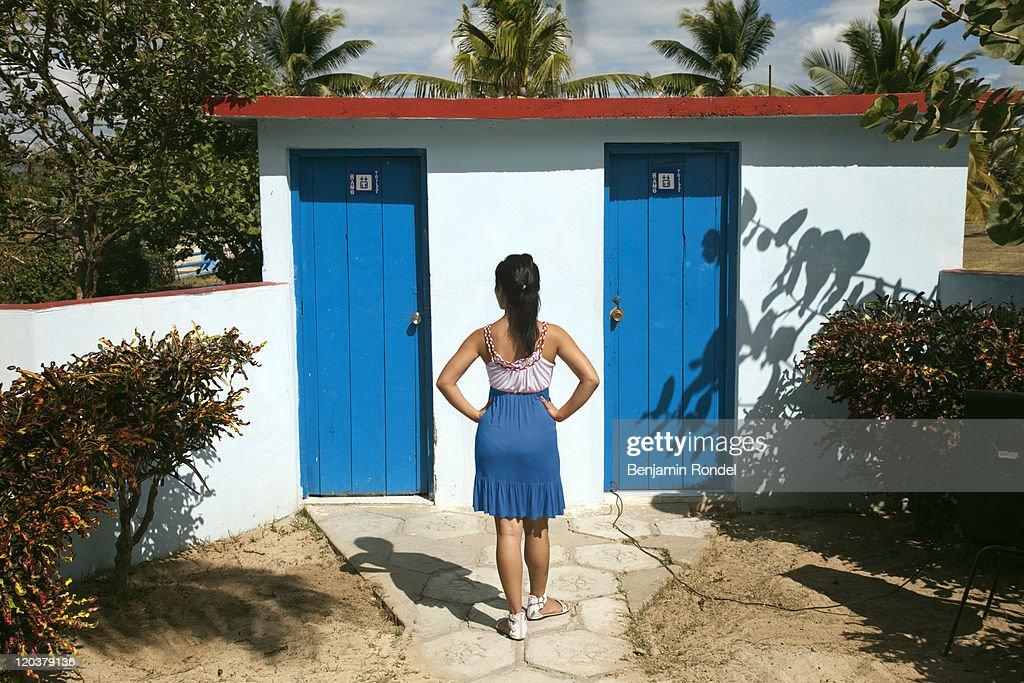 Woman In Front Of Public Bathroom Doors Stock Photo