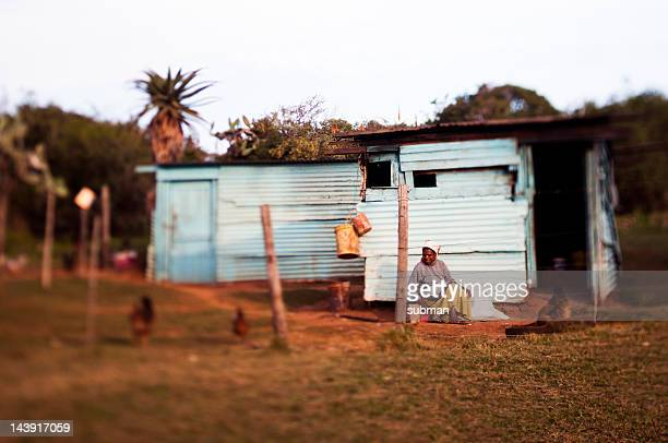 Woman in front of rural house feeding chickens