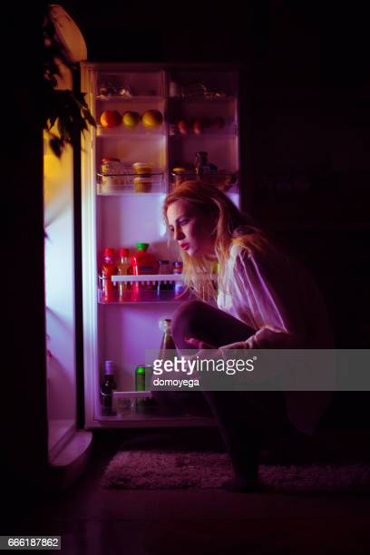 Woman in front of the refrigerator late night